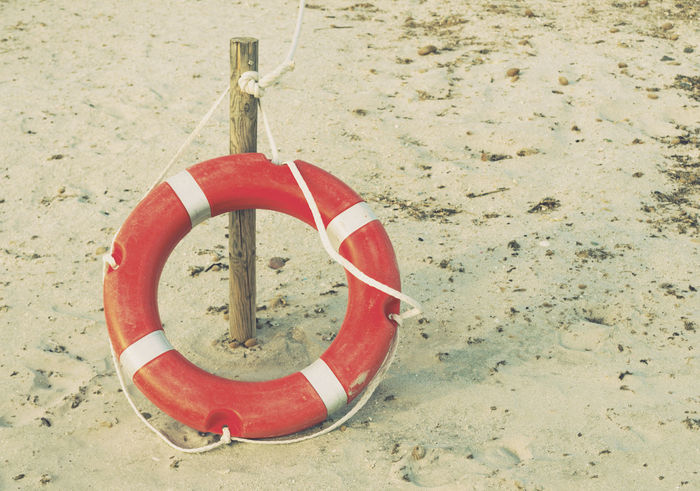 lifebuoy on beach Emergency Post Red Rope Beach Circle Cord Life Belt Life Buoy Life Ring Lifebelt Lifebuoy Lifering Lifesaver No People Outdoors Pole Rescue Retro Styled Safety Sand Shore Tied Up