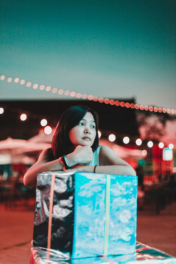 Thoughtful woman leaning on gift box at night