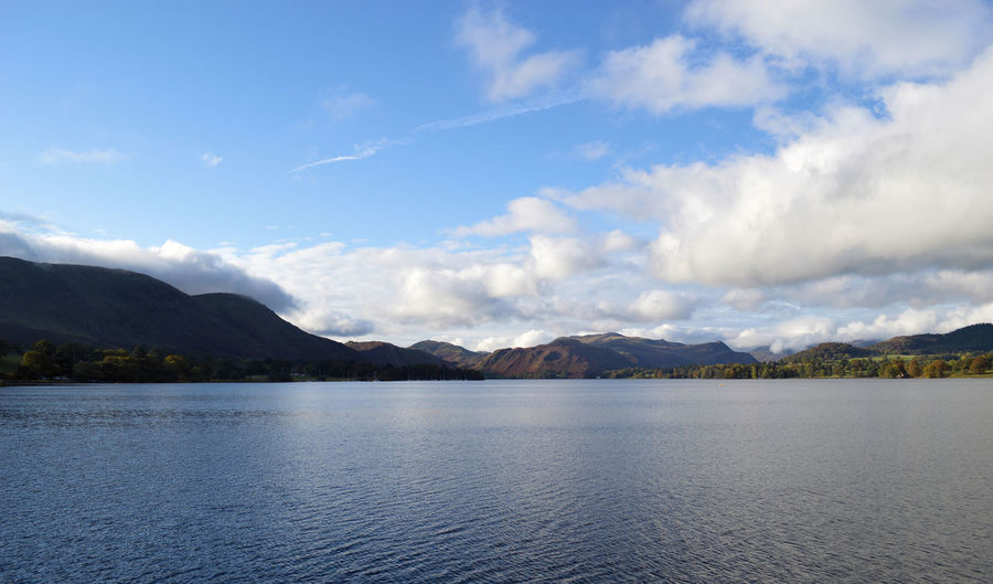 Lake with mountain range against cloudy sky