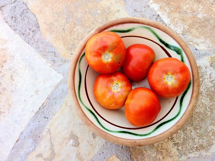 Directly above view of tomatoes in bowl on floor