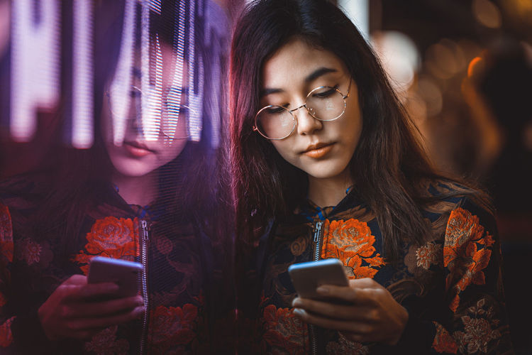 Smiling young woman using smart phone by window with reflection at night