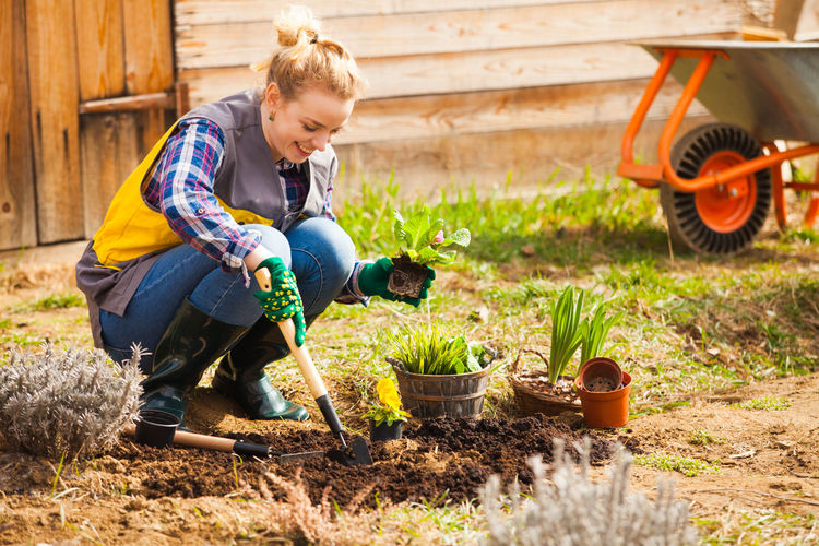 Full length of woman gardening at yard