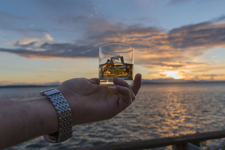 Cropped hand of man holding whisky glass against sea and cloudy sky during sunset