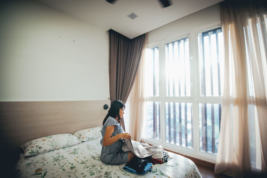 Sitting Window Furniture One Person Indoors  Real People Leisure Activity Domestic Room Lifestyles Full Length Relaxation Casual Clothing Bed Day Curtain Home Interior Adult Domestic Life Young Adult Contemplation