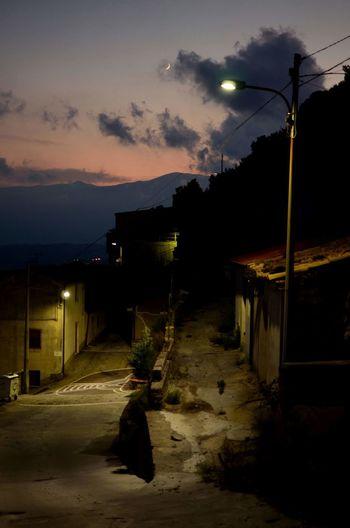 Street amidst illuminated buildings against sky at night