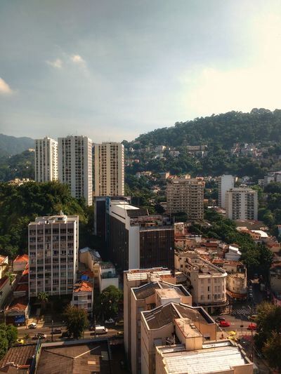 Cityscape of houses and buildings surrounded by lush tropical urban forest with a mountain range in the background. Cityscape Skyscraper House Apartment High Angle View Urban Skyline No People Outdoors Tree Day Sky Forest Brazilian Mountain Range Horizon Tourism Ecology Nature Meets Urban Capital Cities  Urban Jungle Travel Destinations Aereal View Tropical Scenics Landscape