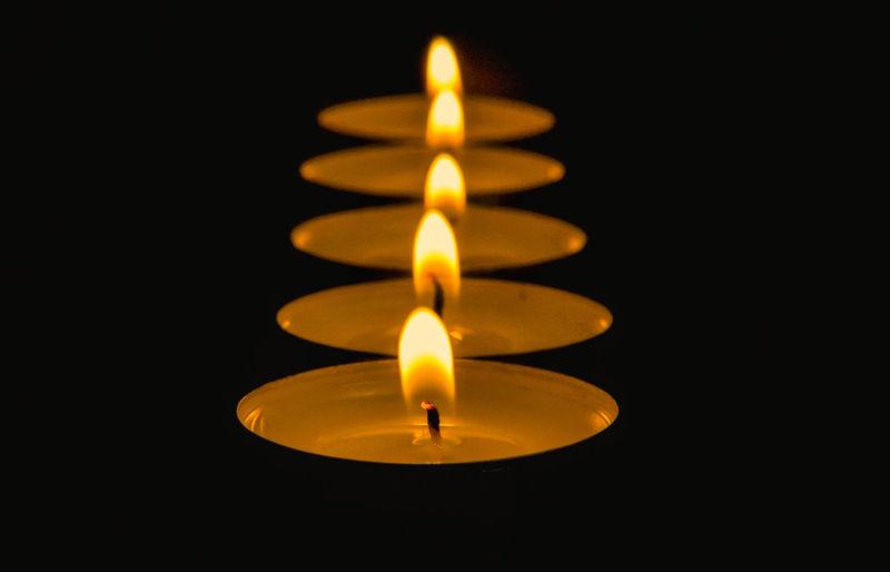 Close-Up Of Illuminated Candle Over Black Background