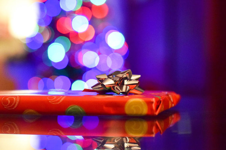 Close-Up Of Wrapped Christmas Present On Table Against Lights