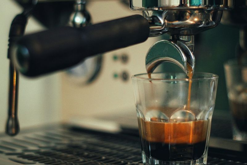 Close-up of coffee pouring in drinking glass