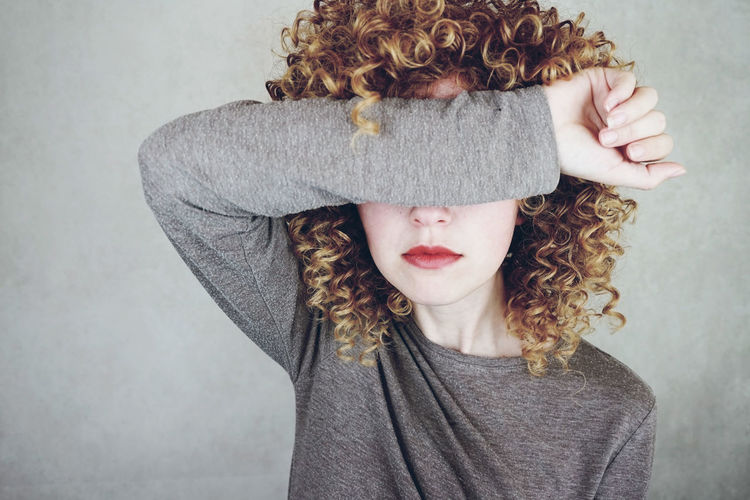 Young woman covering eyes with hand against gray background