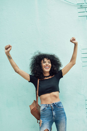 Funny black woman with afro hair raising arms outdoors. Female wearing casual clothes in urban background. Lifestyle concept Afro Arms Raised Beautiful Woman Casual Clothing Curly Hair Emotion Frizzy Front View Hair Hairstyle Happiness Human Arm Leisure Activity Lifestyles Mouth Open One Person Positive Emotion Real People Smiling Standing Three Quarter Length Wall - Building Feature Women Young Adult Young Women