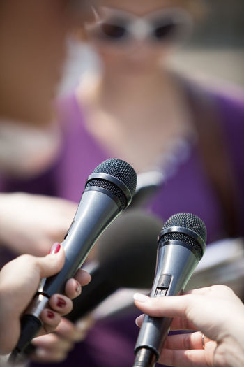 Cropped image of women holding microphones