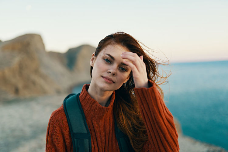 Portrait of beautiful woman at beach against sky