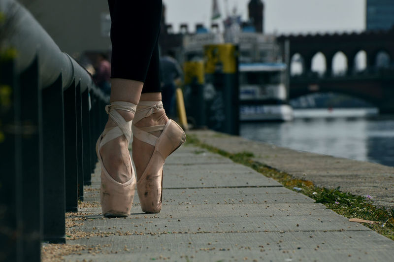 Low section of woman wearing ballet shoes standing on tip toes at promenade