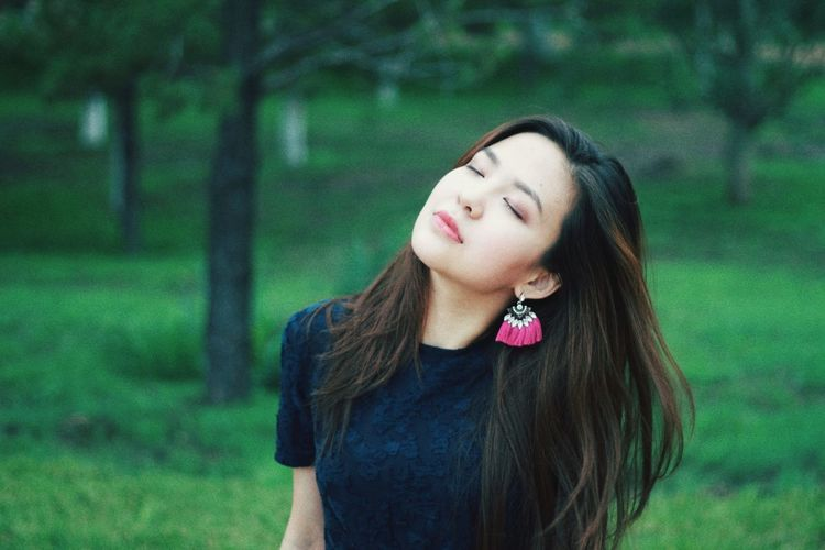Beautiful Young Woman With Eyes Closed Standing In Forest