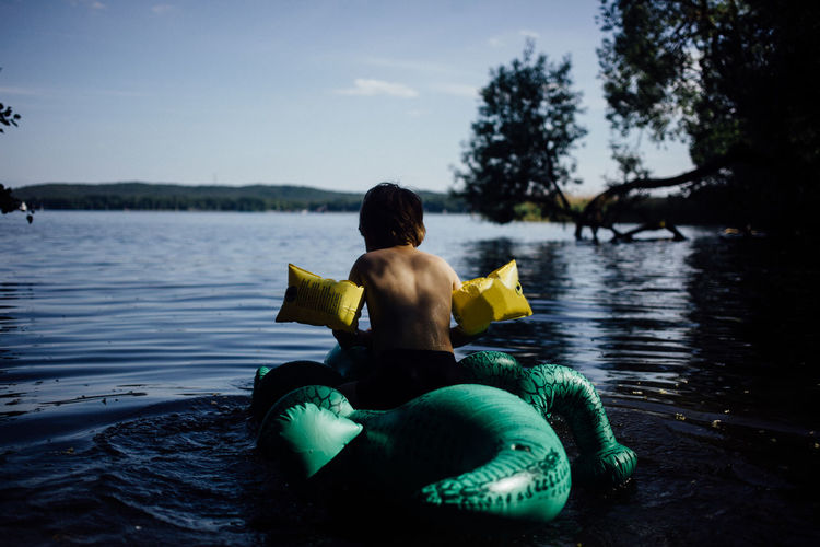 Rear view of boy sitting on inflatable crocodile at lake against sky