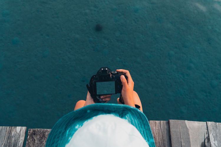 Directly above shot of woman photographing water sitting on pier