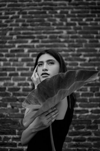 Side view of young woman holding leaf against brick wall