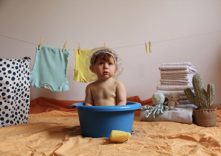 Shirtless Baby Boy Sitting In Bucket At Home