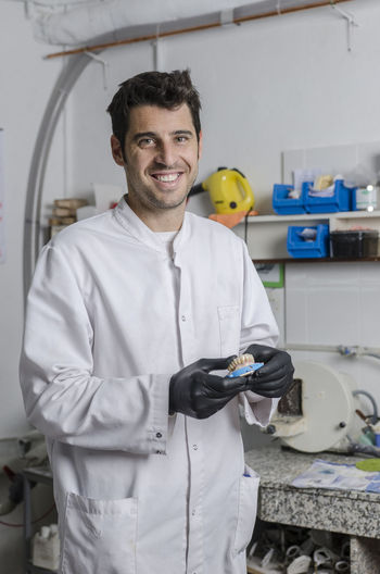 Portrait of smiling dentist holding dentures in laboratory