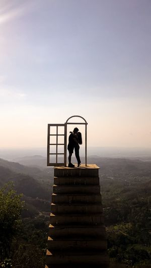 Couple kissing while standing on staircase against sky during sunset