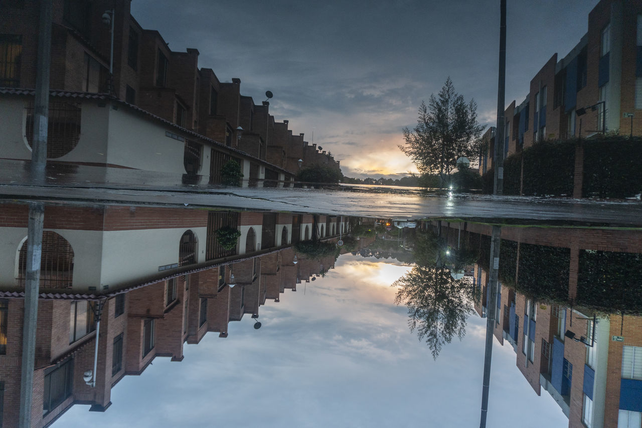REFLECTION OF BUILDINGS IN LAKE DURING SUNSET