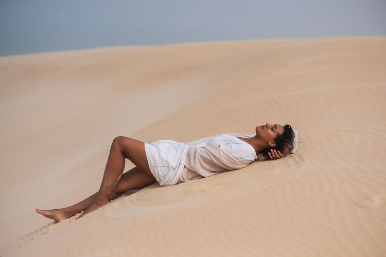 Side view of man lying on sand at beach against sky