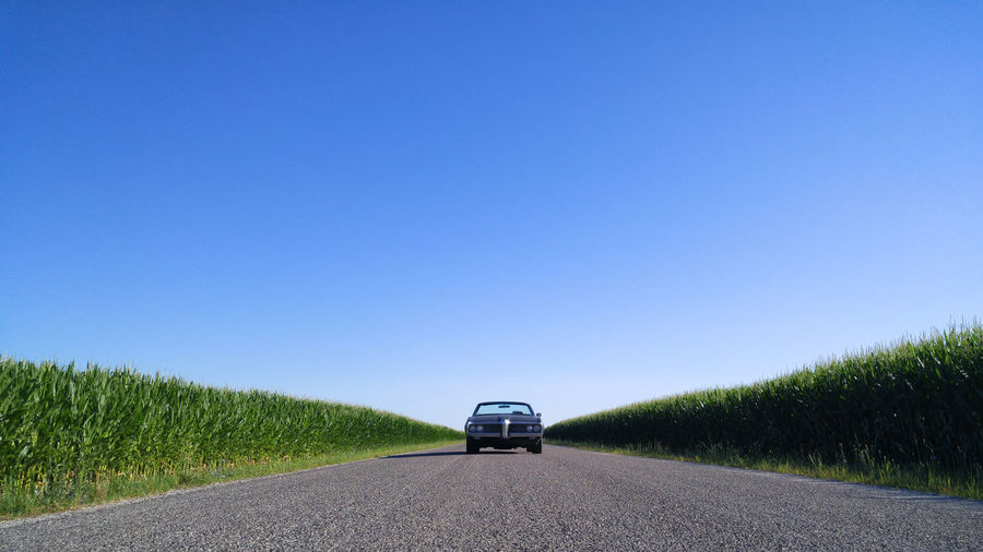 Car on road amidst field against clear blue sky