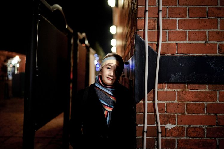 Portrait of woman standing by brick wall at night