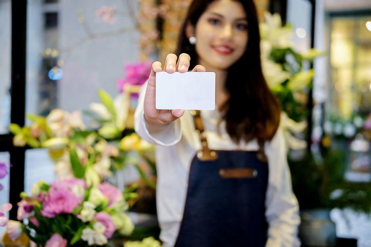 Portrait Of Female Florist Showing Blank Business Card In Flower Shop