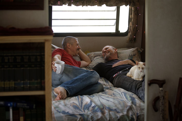 Happy gay couple sleeping on bed in camper van