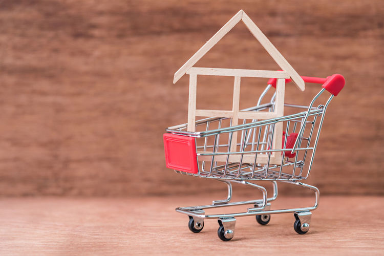 Close-up of model home in shopping cart on table