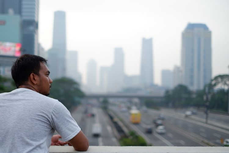 Man looking away against cityscape in city
