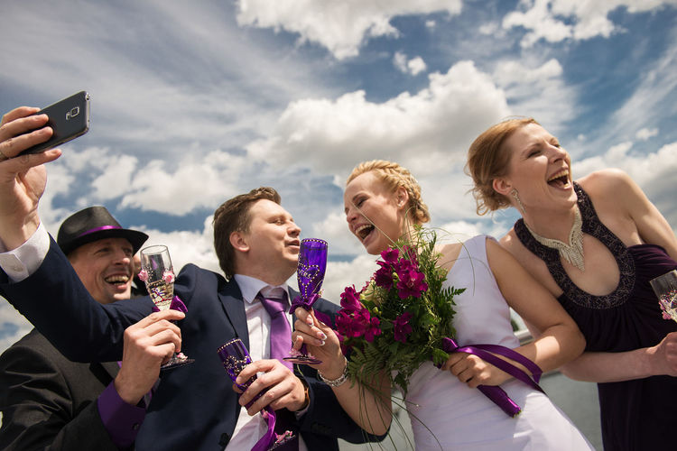 Bridesmaid and best man with bridal couple taking selfie against sky