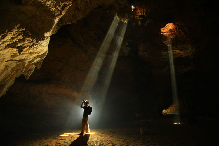 Man Photographing While Standing In Cave