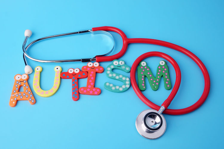 High angle view of multi colored text with stethoscope against blue background