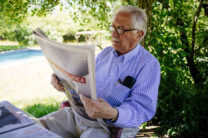 Senior man reading newspaper while sitting against tree