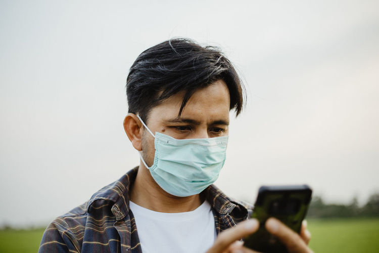 Man using mobile phone while wearing mask against sky