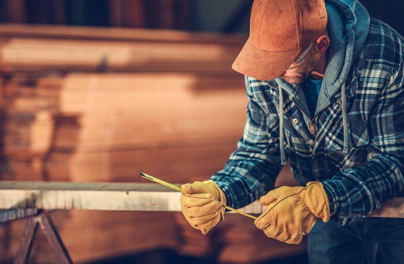 Carpenter measuring in workshop