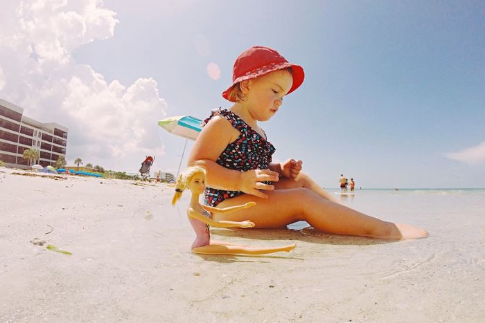 Full Length Beach Sky Childhood Sand Leisure Activity Outdoors One Person Real People Vacations Day Sea Water Lifestyles Sitting Summer Sun Hat Nature Sand Pail And Shovel