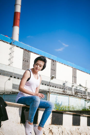 Young woman sitting on barricade against factory