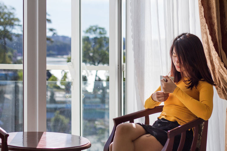 Young woman having drink in cup while sitting on chair at home