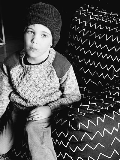 Portrait Of Boy Wearing Warm Clothing Sitting At Home