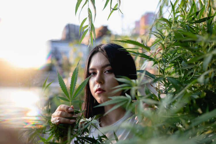 Portrait of young woman amidst plants