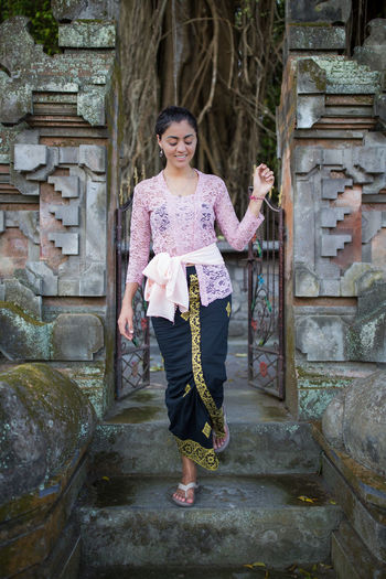 Full Length Of Beautiful Young Woman In Traditional Clothing Moving Down Steps