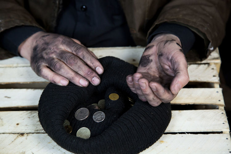 Midsection of beggar with coins in knit hat