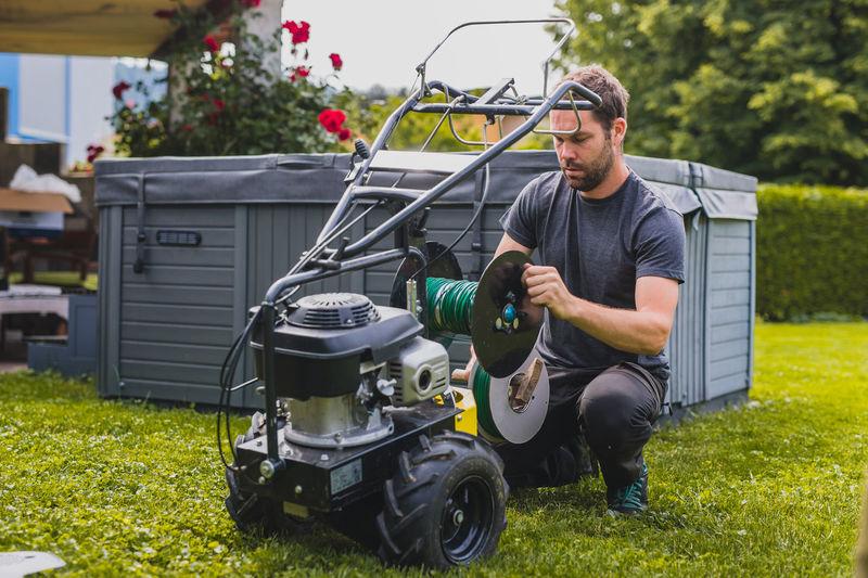 Man repairing lawn mower at yard
