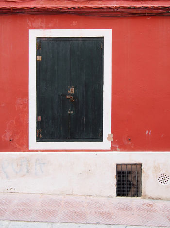 old dark green wooden closed shutters in a white framed window in an old distressed red painted wall Window Shutter Red Color Building Exterior Architecture Red Built Structure Wall - Building Feature No People Outdoors Closed Residential District House City Day