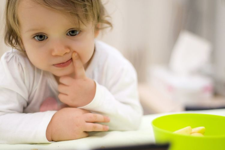 Portrait of cute baby girl sitting on table at home