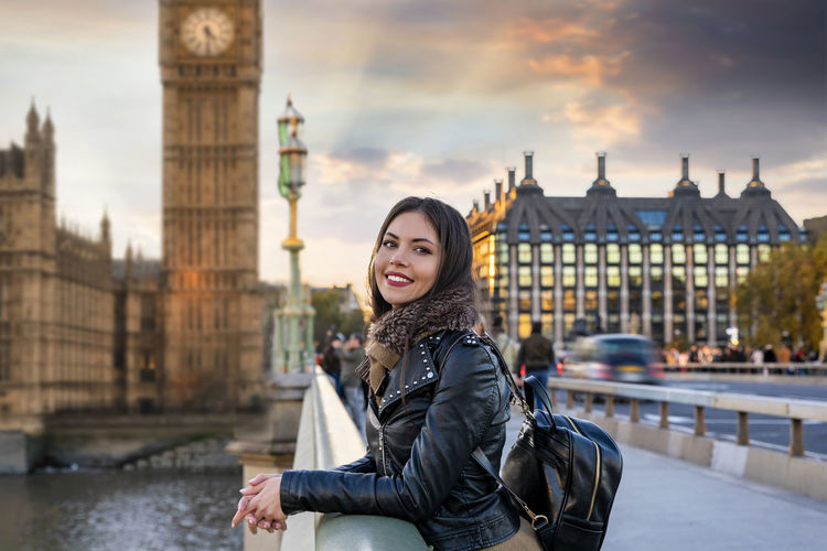 Portrait Of Smiling Young Woman Standing Against Tower Bridge In City During Sunset
